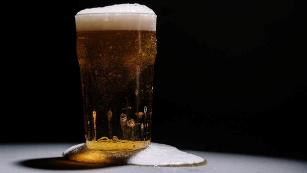 Image of beer in a pint glass with foam having spilled over the side