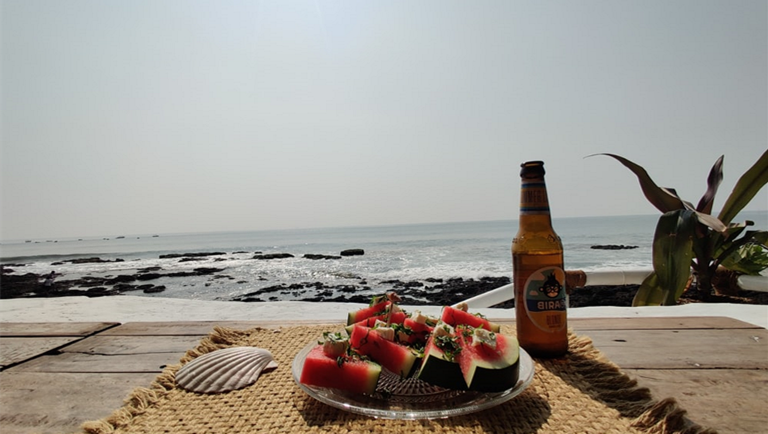 Image of a bottled beer with a plate of watermelon at the beach
