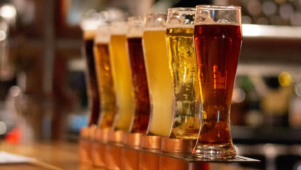 Image of a flight of seven beers lined up on a bar