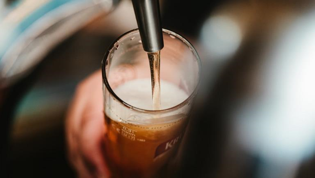 Image of beer coming into a glass from the tap