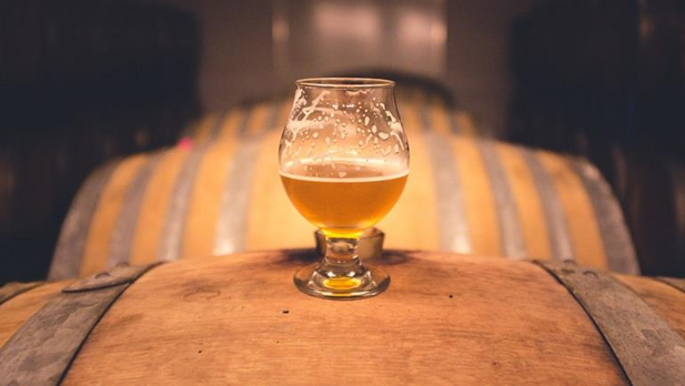 Image of beer in a snifter sitting on a barrel