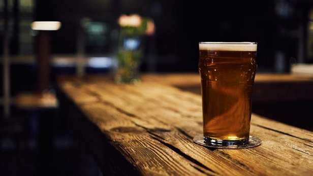 Image of a glass of beer on a wooden bar