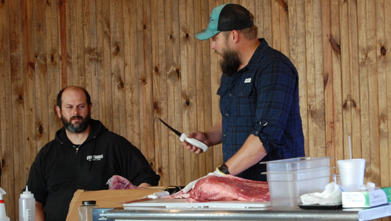 Image of Arnis Robbins trimming brisket with Nathan Pier
