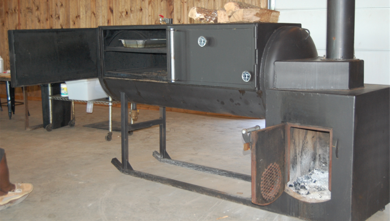 Image of reverse flow smoker with a water pan on the furthest end from the firebox