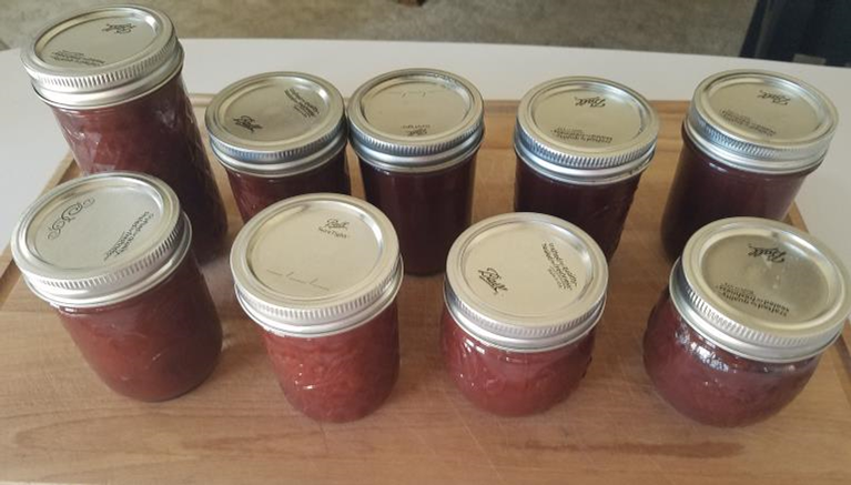 Crabapple butter in various sizes of jars sitting on a wooden cutting board.