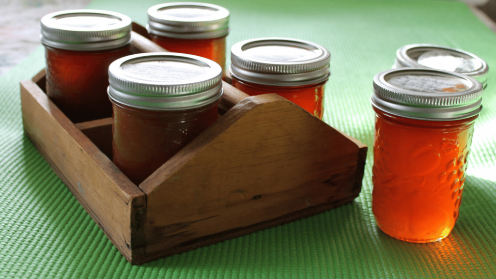 Home canned crab apple butter and jelly in jars which are arranged in a wooden carrier that is sitting on a green tablecloth.