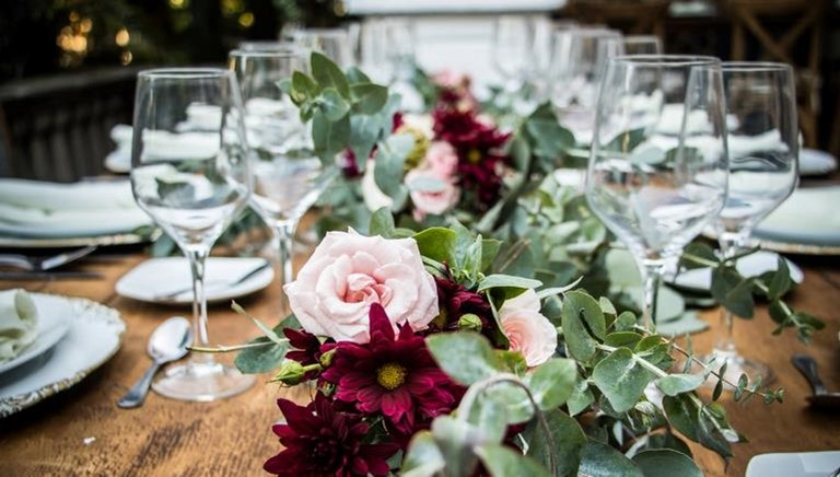 Photo of a low flower arrangement of pink, burgundy, and greenery on a wooden table with wine glasses and gold-rimmed white china. This image represents choosing an appropriate centerpiece when learning how to set a table.