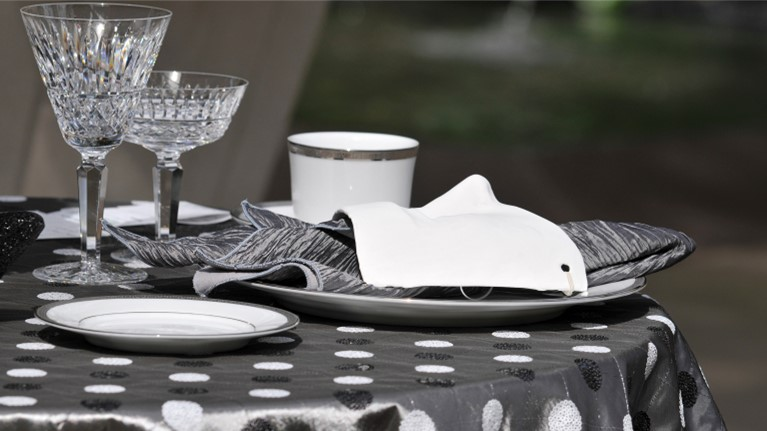 Photo of fine china and crystal wine glasses on a silver tablecloth with black and white sequined polka dots. A silver silk napkin lays on top of a dinner plate. This image represents choosing the table linens carefully.