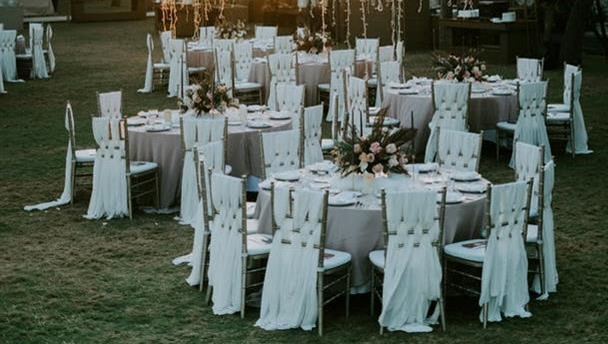 Photo of six round tables beautifully set in white, gold, and blush for an outdoor event. This image represents proper spacing around and between tables.